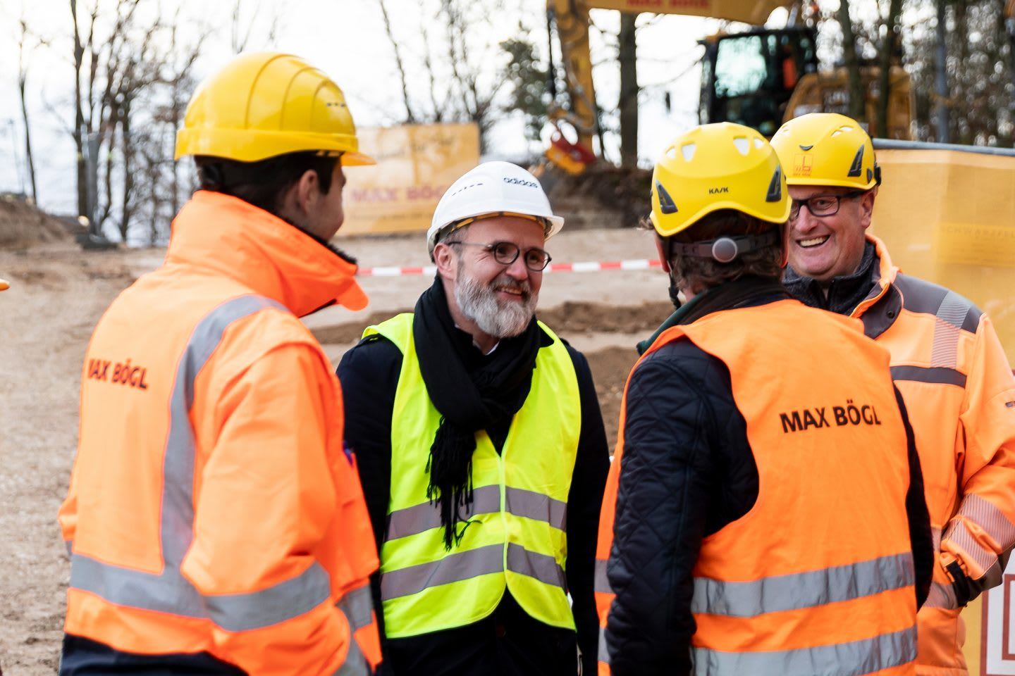 A group of four men standing and chatting on the construction site of the basecamp for the Germany national football team at adidas headquarters. Home Ground, football, Germany, adidas headquarters, teamwork, GamePlan A.
