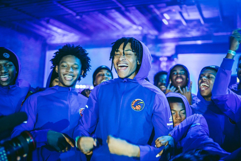 A mens sports team with blue jackets celebrating together. team work, sports, basketball, joy, celebration, GamePlan A.