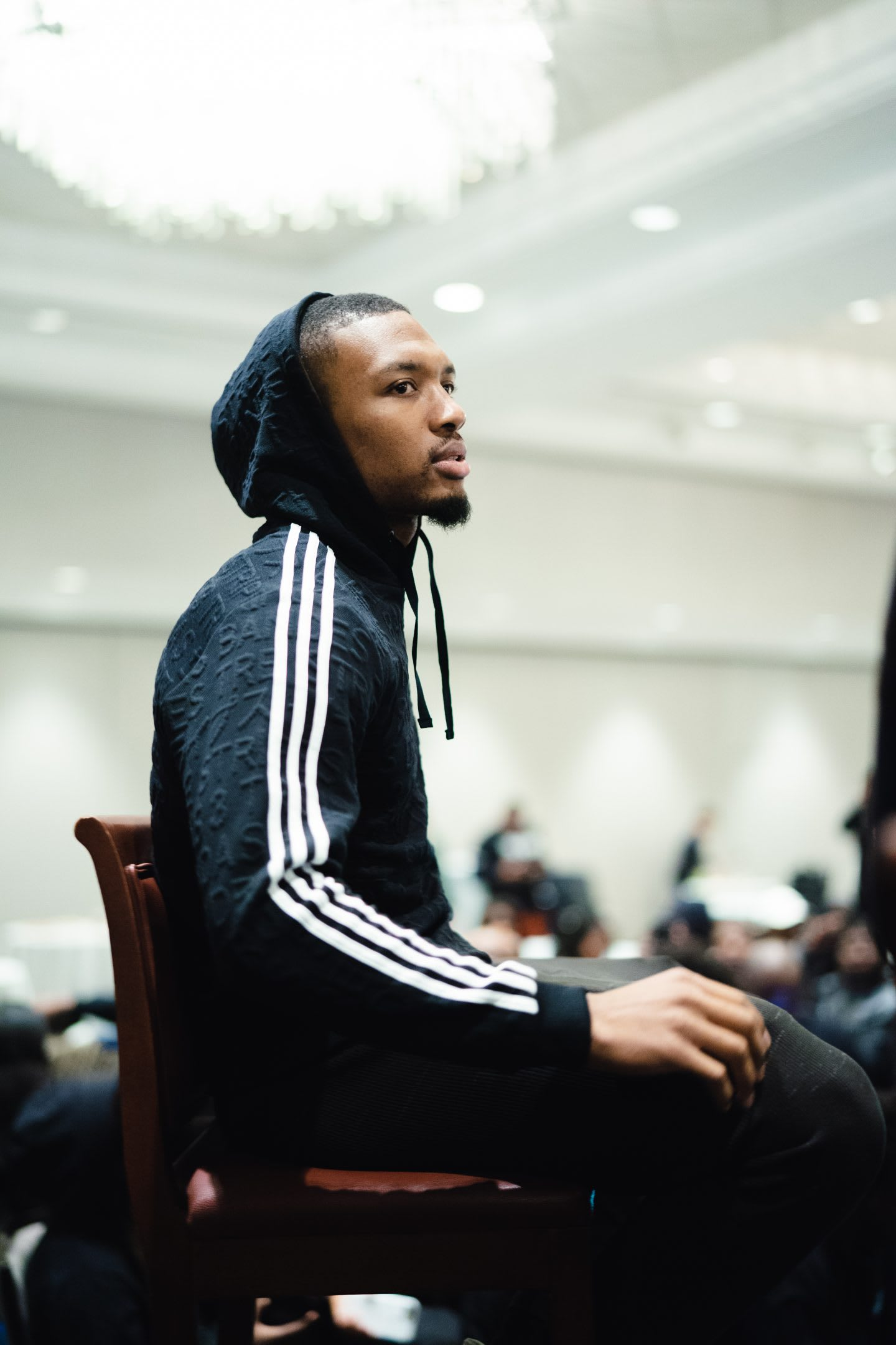 US basketball player Damian Lillard sitting on a chair wearing a black adidas hoodie. Dame, Dame Time, basketball, sports, leadership, role model, icon, GamePlan A.