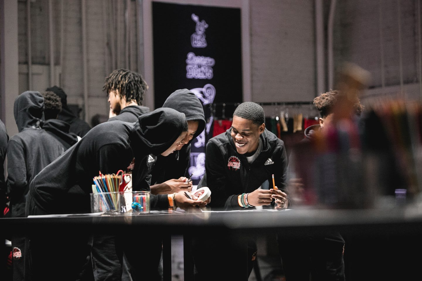 Three young man standing at a desk laughing together at a conference. Sports, Team work, collaboration. achievements, success, GamePlan A.