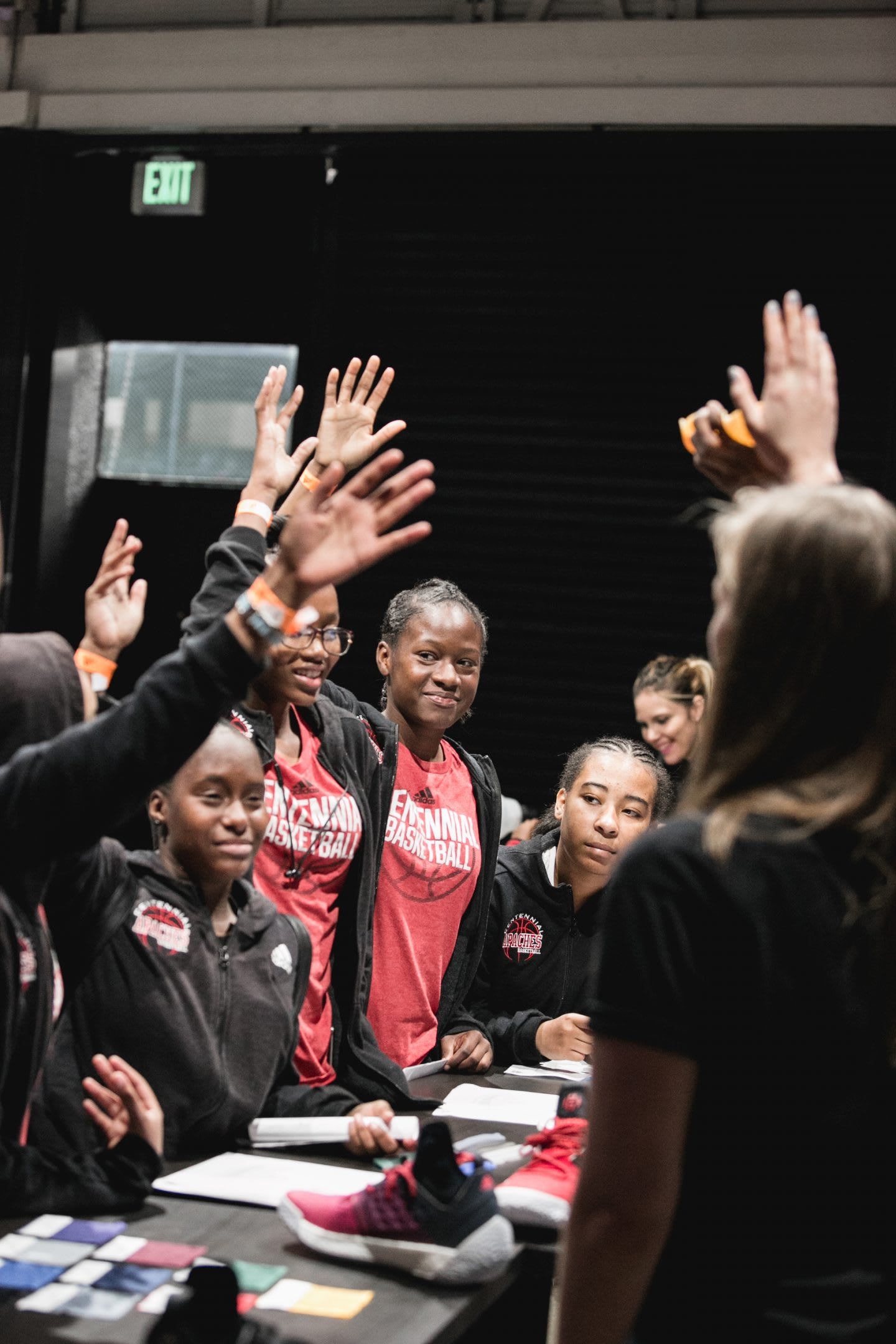 Young women standing at a desk and raising their hands. Sports, Team work, collaboration. achievements, success, GamePlan A.