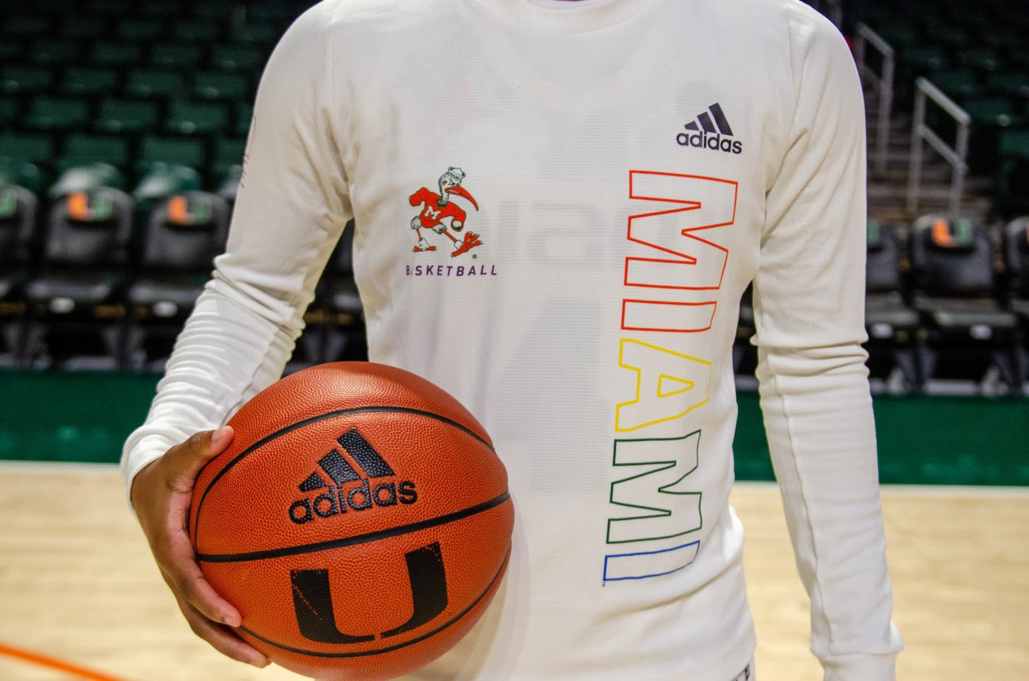 A women holding a basketball and wearing a white shirt with pride colored letters.