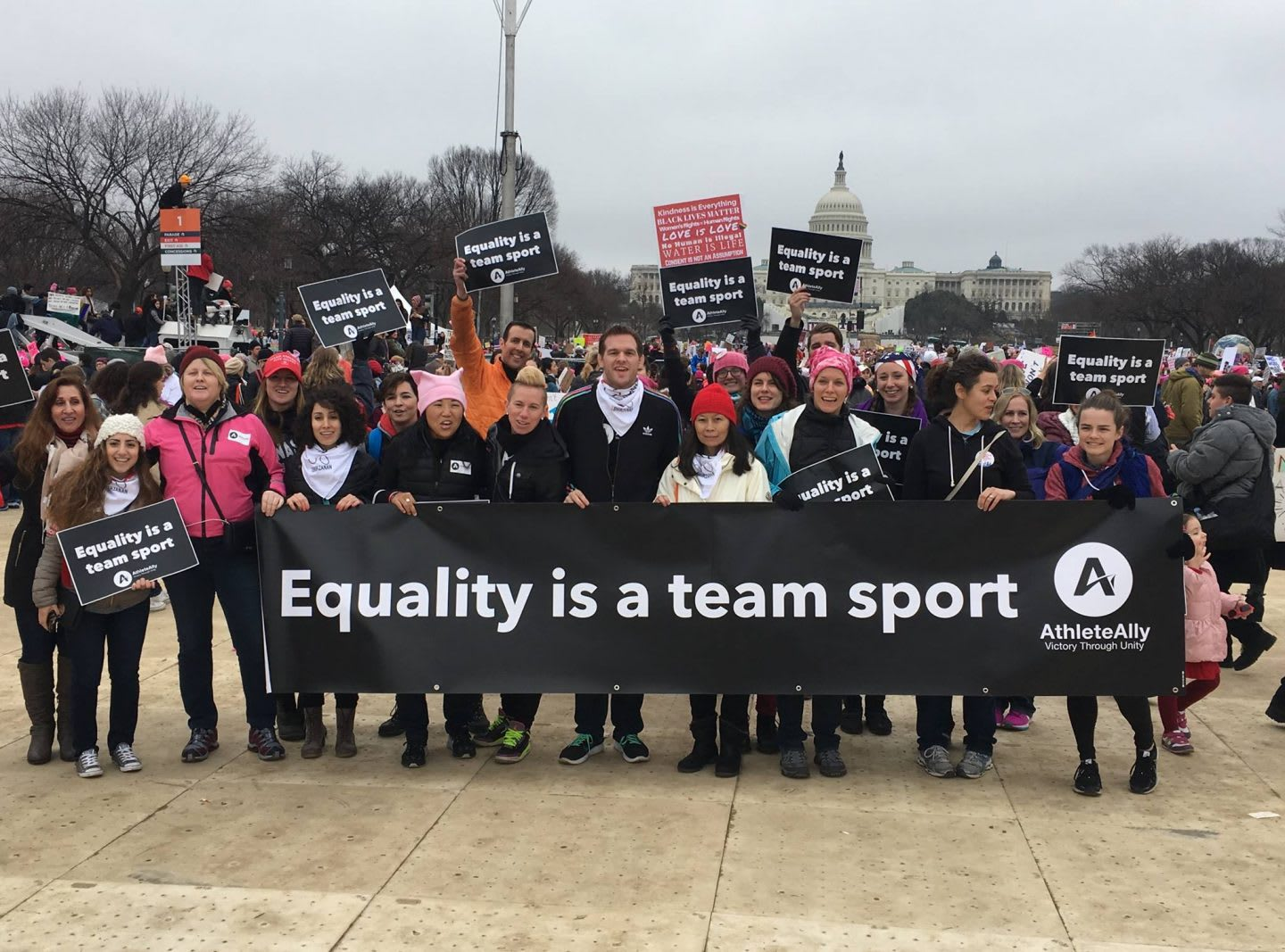 A group of people standing in front of the US Capitol holding a sign together which says: