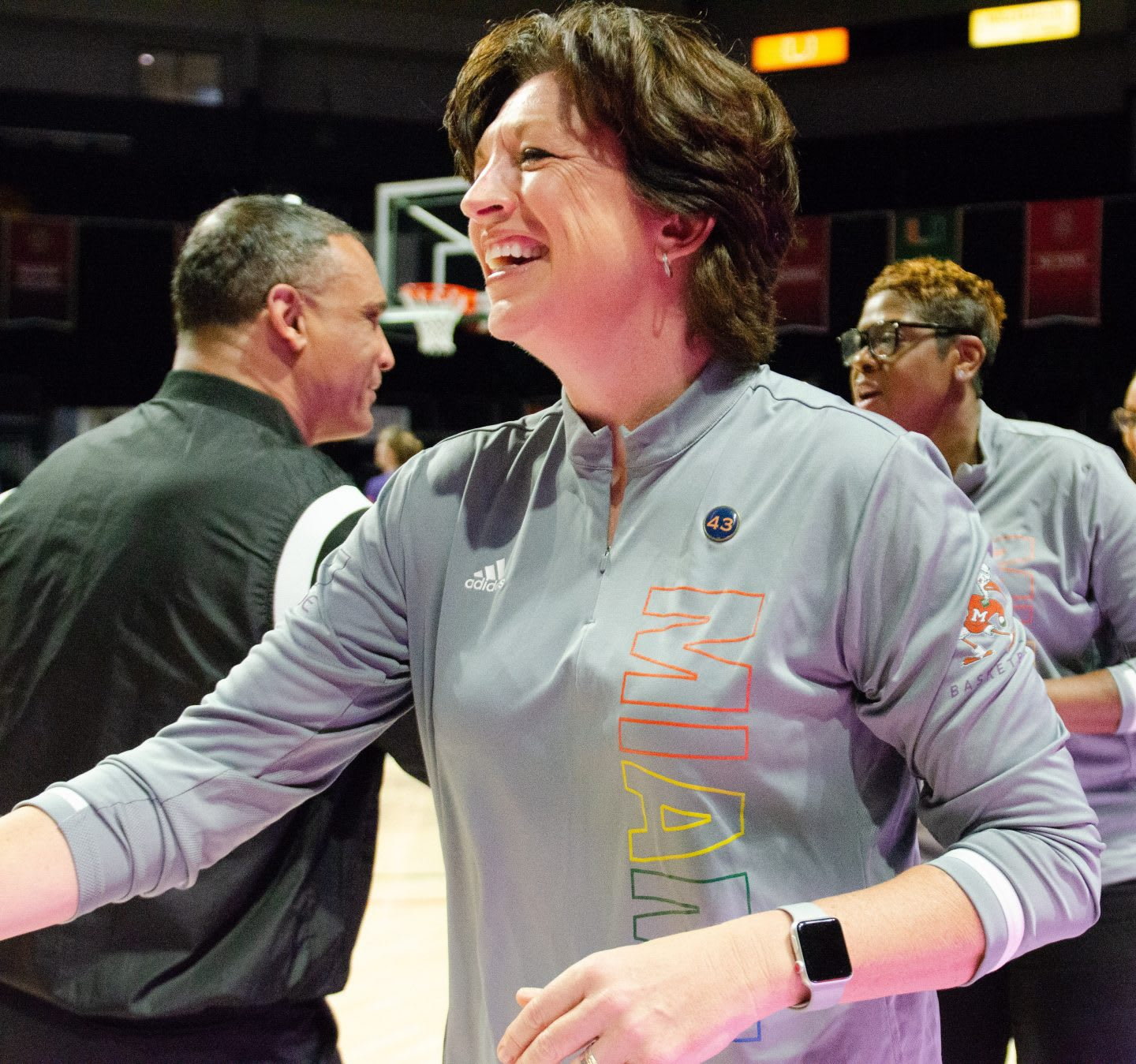 The coach of the University of Miami Womens Basketball Team smiling and wearing a grey shirt with pride colored letters. Pride, Sports, Athletes, Ally, Basketball, GamePlan A.