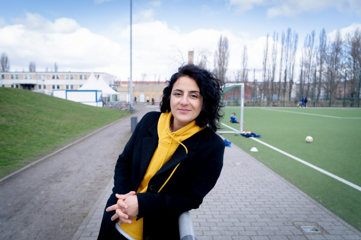 Tugba standing in front of a football field. football, community, girls,, playing football