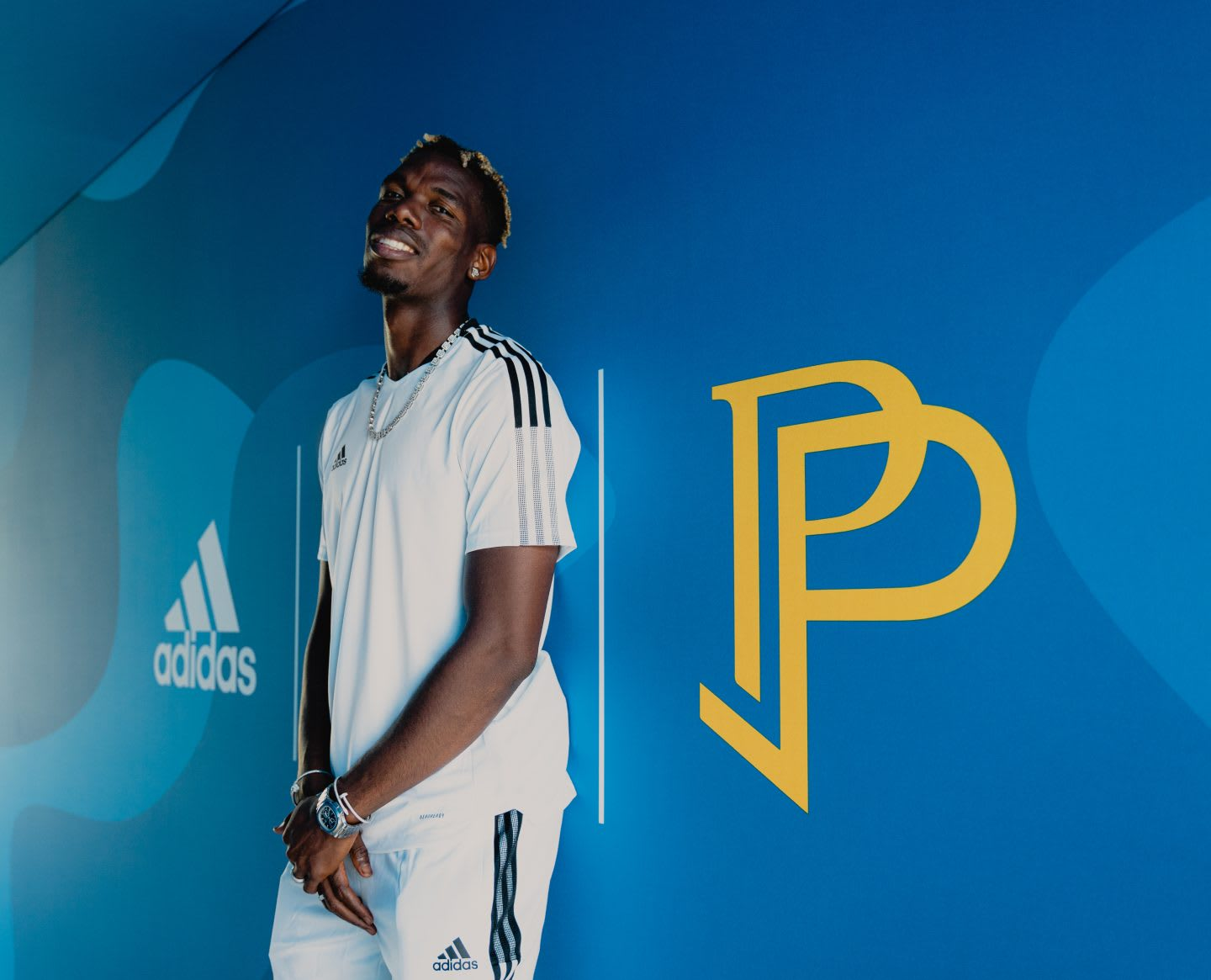 Paul Pogba standing on a wall painted with his logo. Football, legend, adidas, star,, playing football