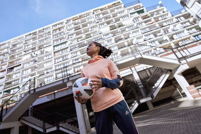 Woman holding a football in front of a building. Playing football, woman, sports, community, inclusion, emporement