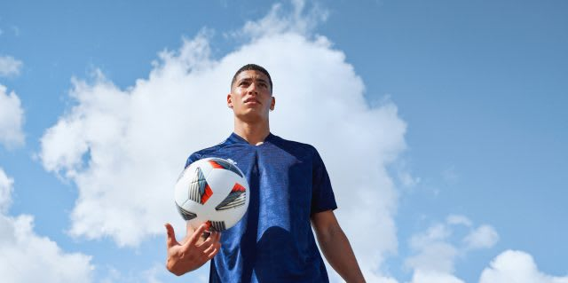 Player holds football with the sky in the back. Football, mindset of a champion, success, career, improving performance