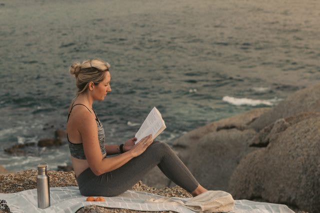 Woman reads a book while sitting on the rocks next to the ocean. Reading, Champion's Mindset, summer, reading list, mindset