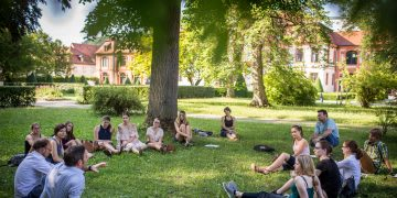 Students discussing and learning in a circle on the grass on a university campus, learning, outdoor, nature, workplace