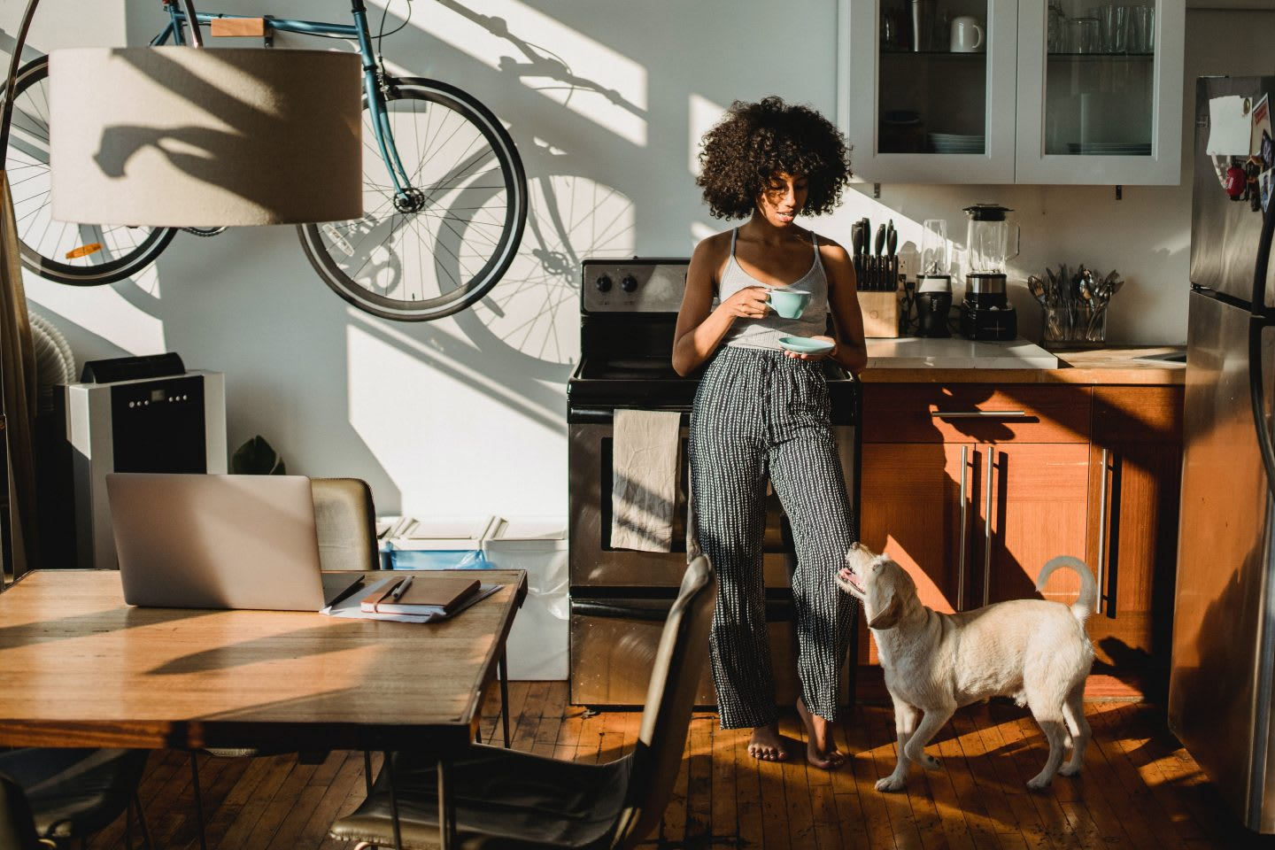 Woman standing in the kitchen with a coffee and a dog. Virtual meetings, home office, working from home,