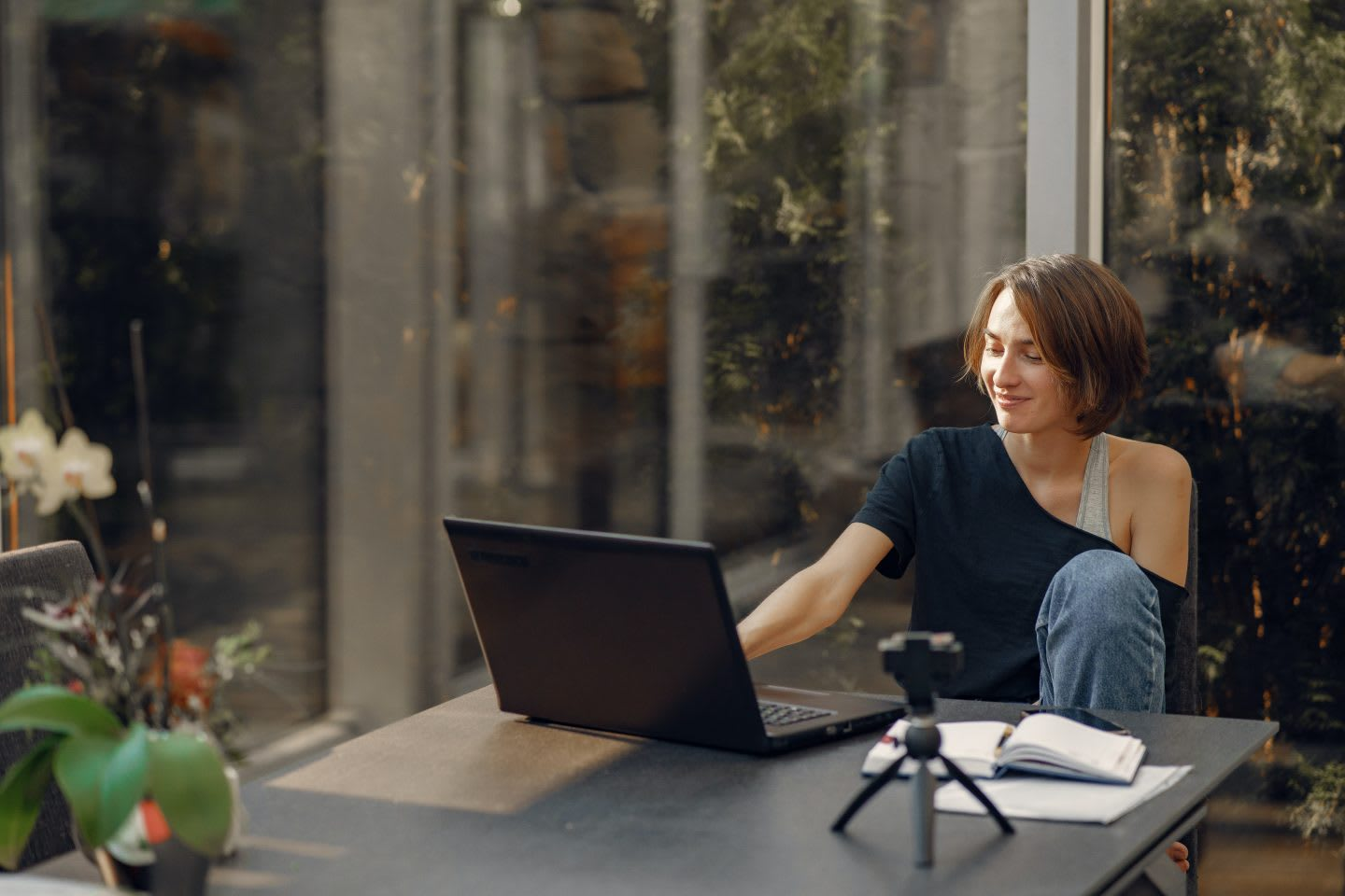 Woman sitting on a desk next to a window working on a laptop. Virtual meetings, work remotely, home office