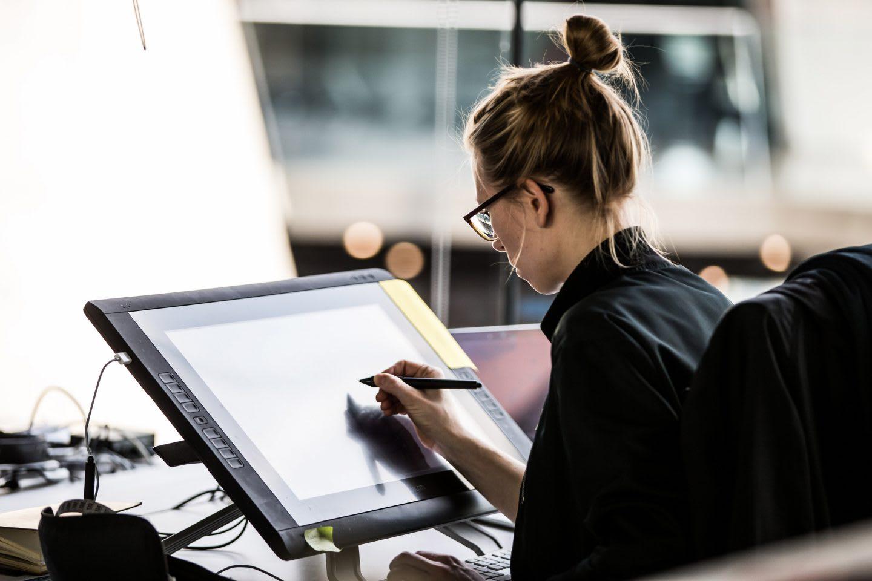 Blonde woman drawing on a digital sketchpad in an office, employee, design, adidas, work, creativity, digital