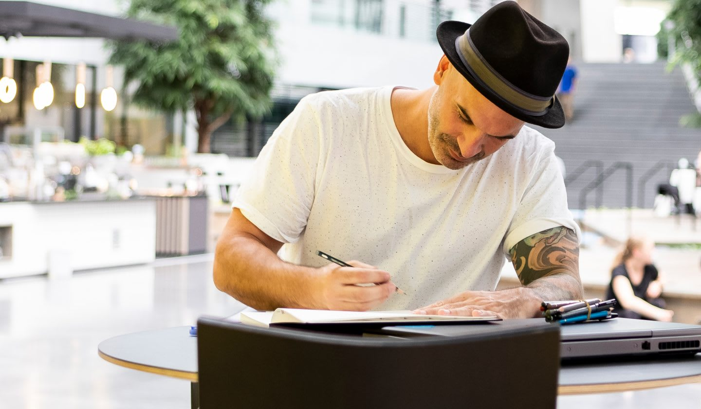 Man wearing hat and white t-shirt writing in notebook, employee, adidas, HQ, worklife