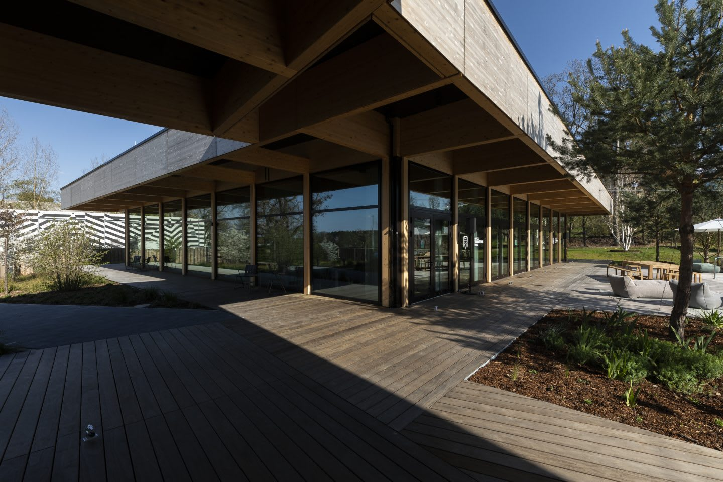 Image of low-rise building with wooden paths, HOMEGROUND, adidas, HQ, headquarters, Herzogenaurach, Germany