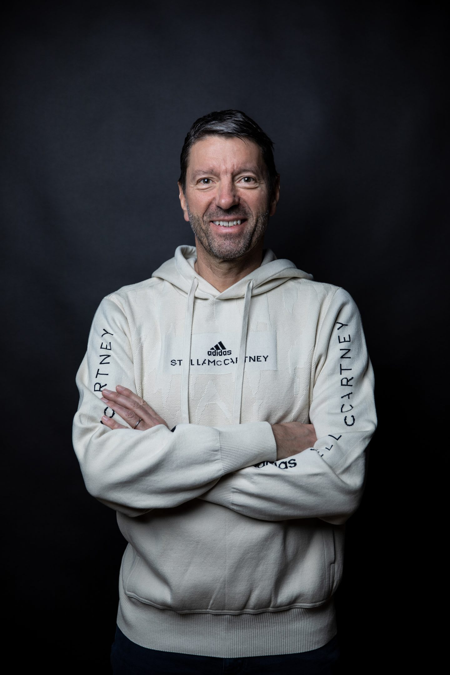 Man wearing white hooded sweatshirt standing with arms folded, Kasper, Rorsted, CEO, adidas, sports, company