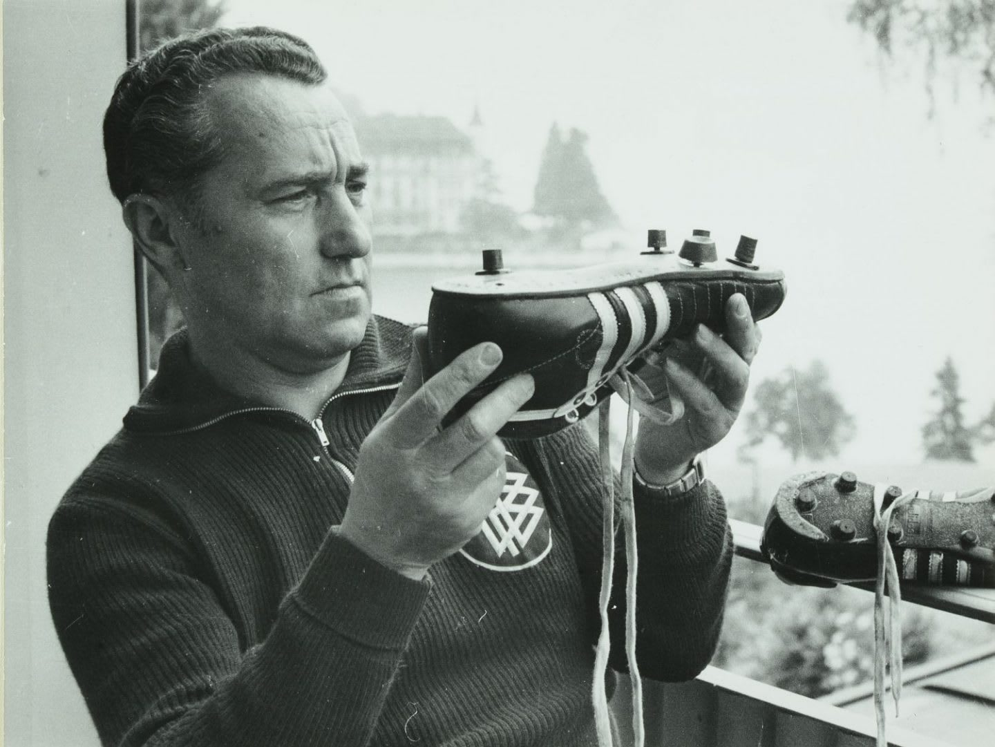 Man holding football shoe up close to his face for inspection, Adi, Adolf, Dassler, adidas, shoe, company, history, shoemaker