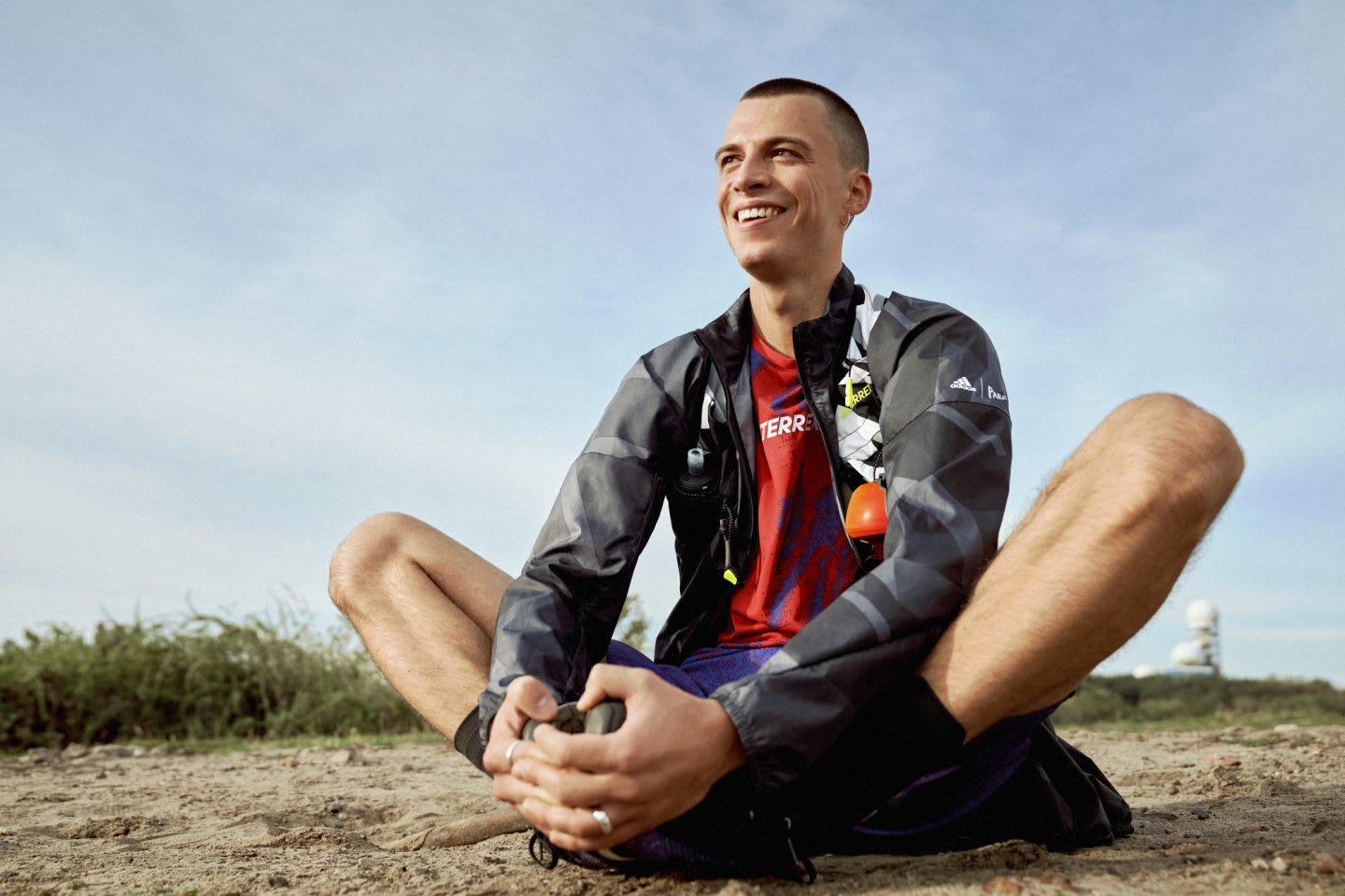 Man smiling in the outdoors while doing butterfly pose, stretching, sports, sport, fitness, adidas