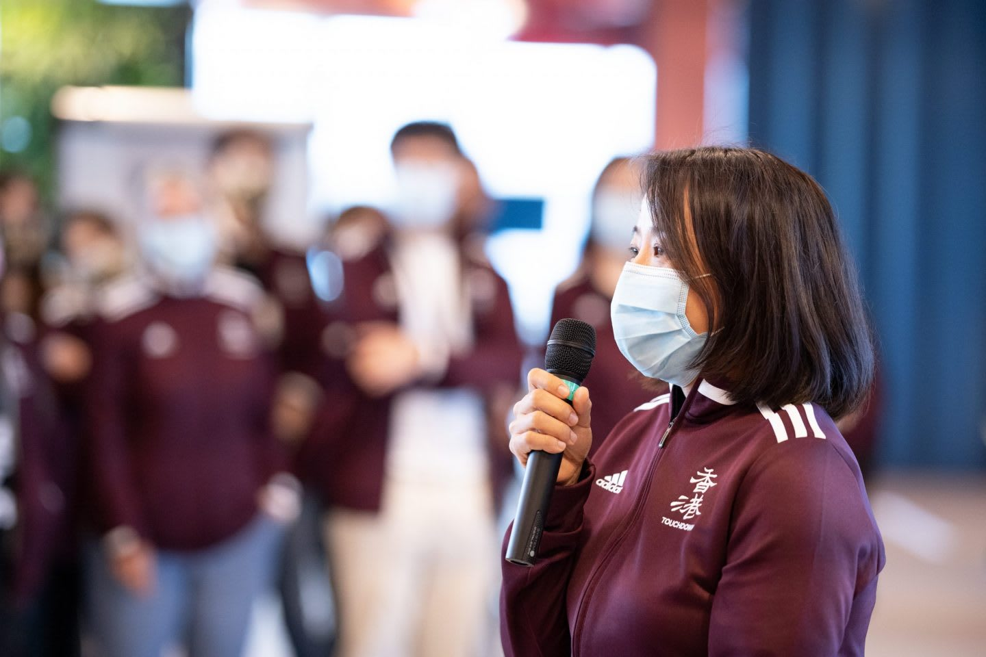 Woman wearing a medical mask holding a microphone speaking in front of a crowd, Hoa Ly, adidas, employee, Sourcing, Asia, leadership, leaders, women
