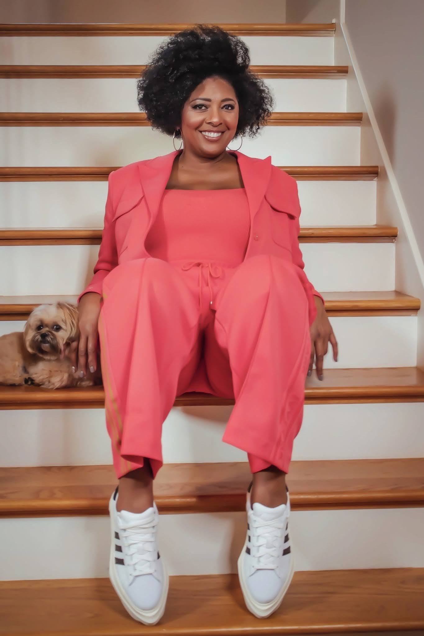 Woman wearing a pink suit sitting on stairs smiling, Vicky Free, marketing, adidas, employee, leadership, leaders, women