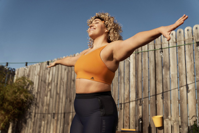 Woman wearing an orange sports bra stretching arms apart, adidas, women, training, apparel, sports, sport, fitness