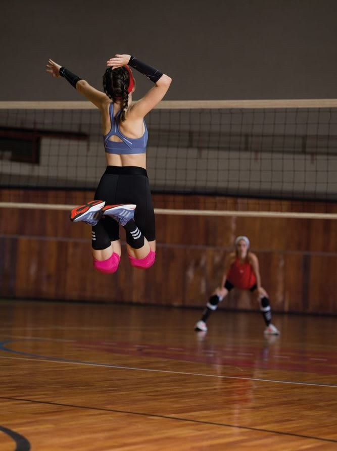 Girl jumping up to hit the ball over the net during volleyball match, adidas, sports, girl, women, training, fitness