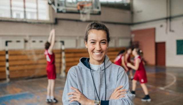 Woman smiling with arms crossed in grey sweatshirt on basketball court, women, girl, leader, sports, sport
