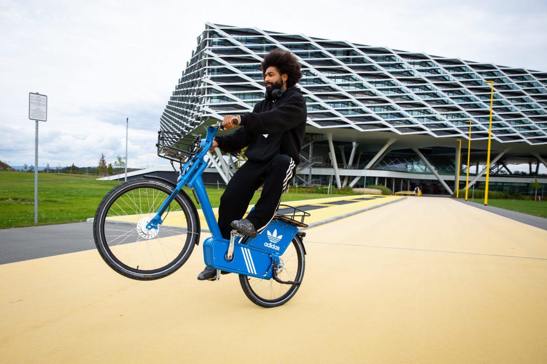 Man wearing black doing one-wheel trick on blue adidas Originals bike, adidas, HQ, headquarters, Herzogenaurach, Germany, sports, company