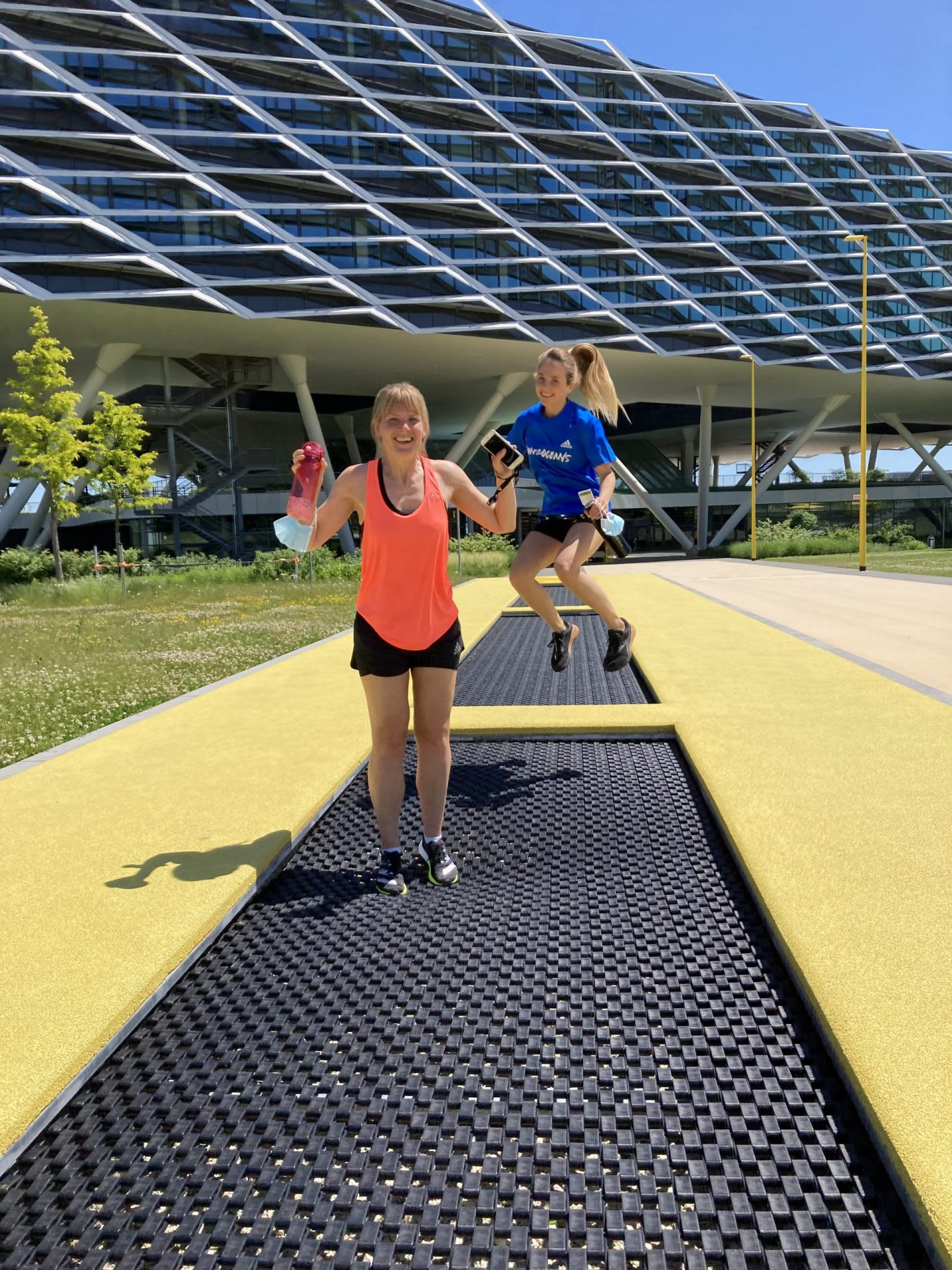 Women jumping on trampoline in front of a large building, adidas, HQ, headquarters, Herzogenaurach, Germany, sports, company