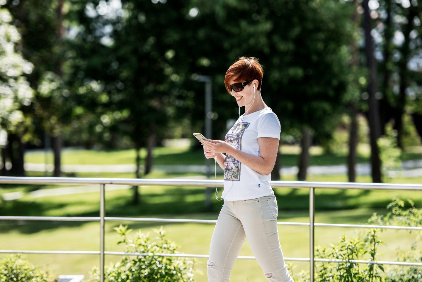 Woman in white t-shirt walking outdoors while looking at phone, nature, green, break