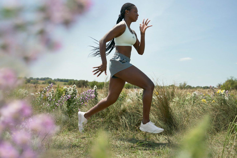 Woman wearing sports bra and shorts running in a field, adidas, FUTURECRAFT.FOOTPRINT, FUTURECRAFT, innovation, sustainability, carbon, adidas