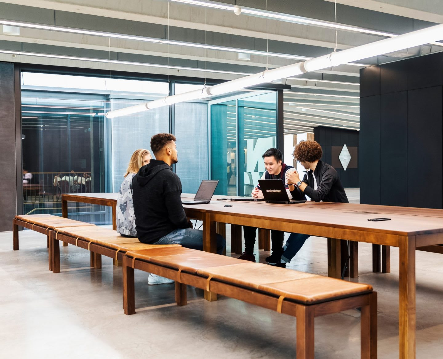 Men and women working at a table on laptops while discussing ideas, adidas, employees, workplace, culture, headquarters