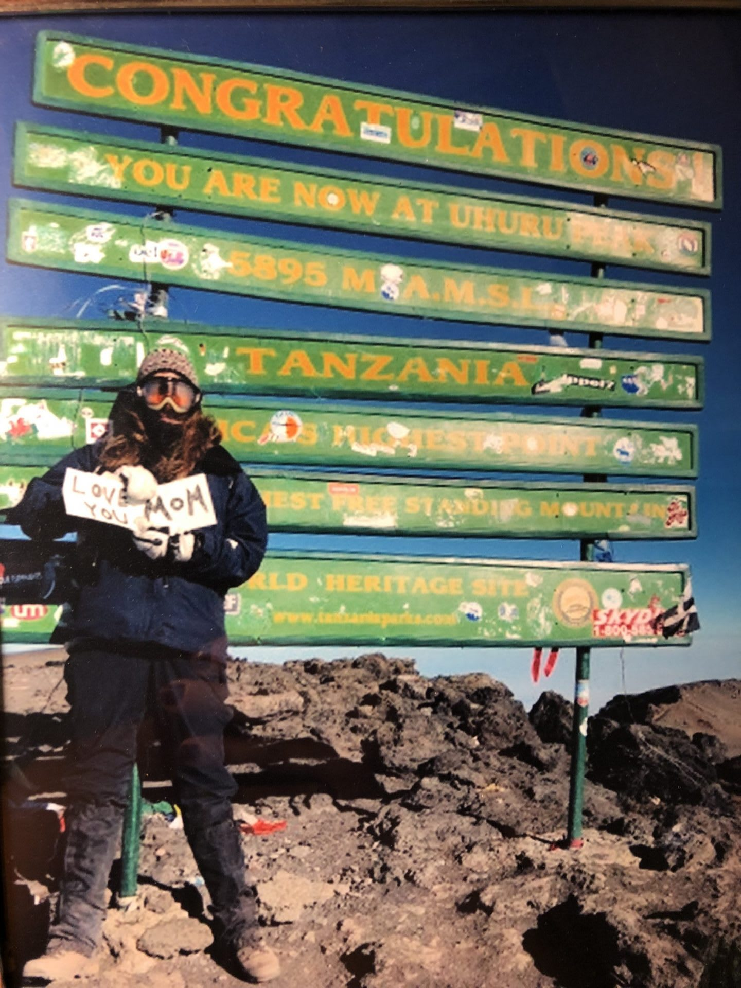 Woman standing on top of Kilimanjaro mountain holding a sign, Samantha Jacobs, adidas, employee, Senior Manager