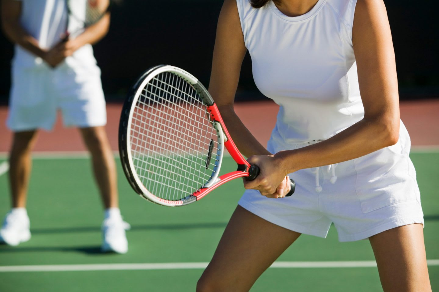 Woman wearing tennis whites holding a tennis racket during a doubles game, sports, sport, tennis, players
