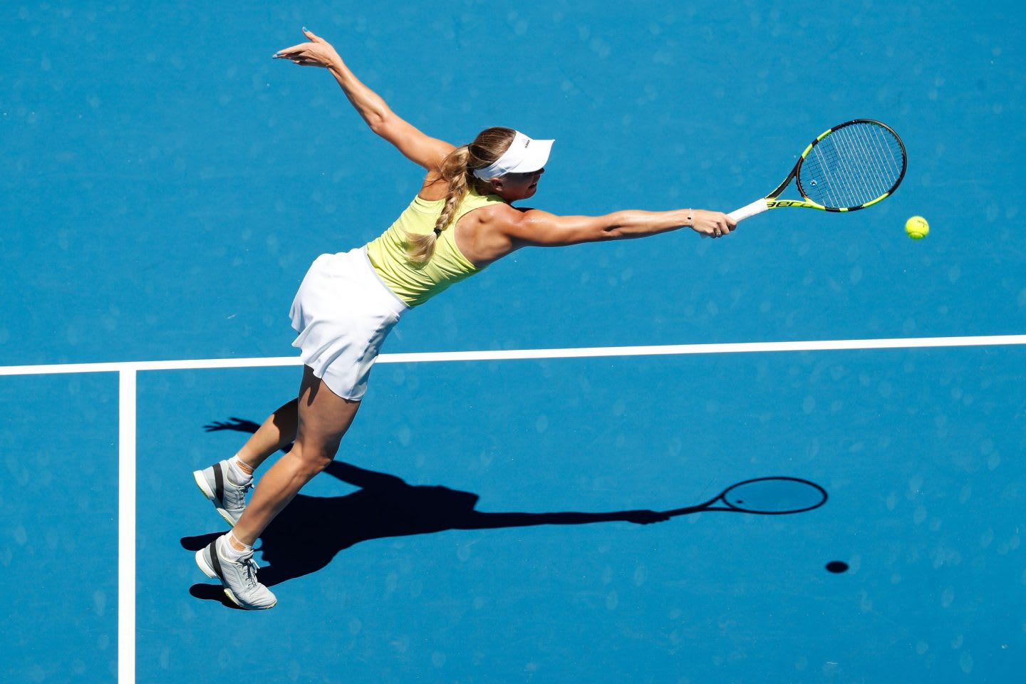 Woman wearing a yellow and white tennis outfit hitting a tennis ball with a racket on a blue court, Caroline Wozniacki, tennis, player, Danish, athlete, adidas, Australia, Melbourne