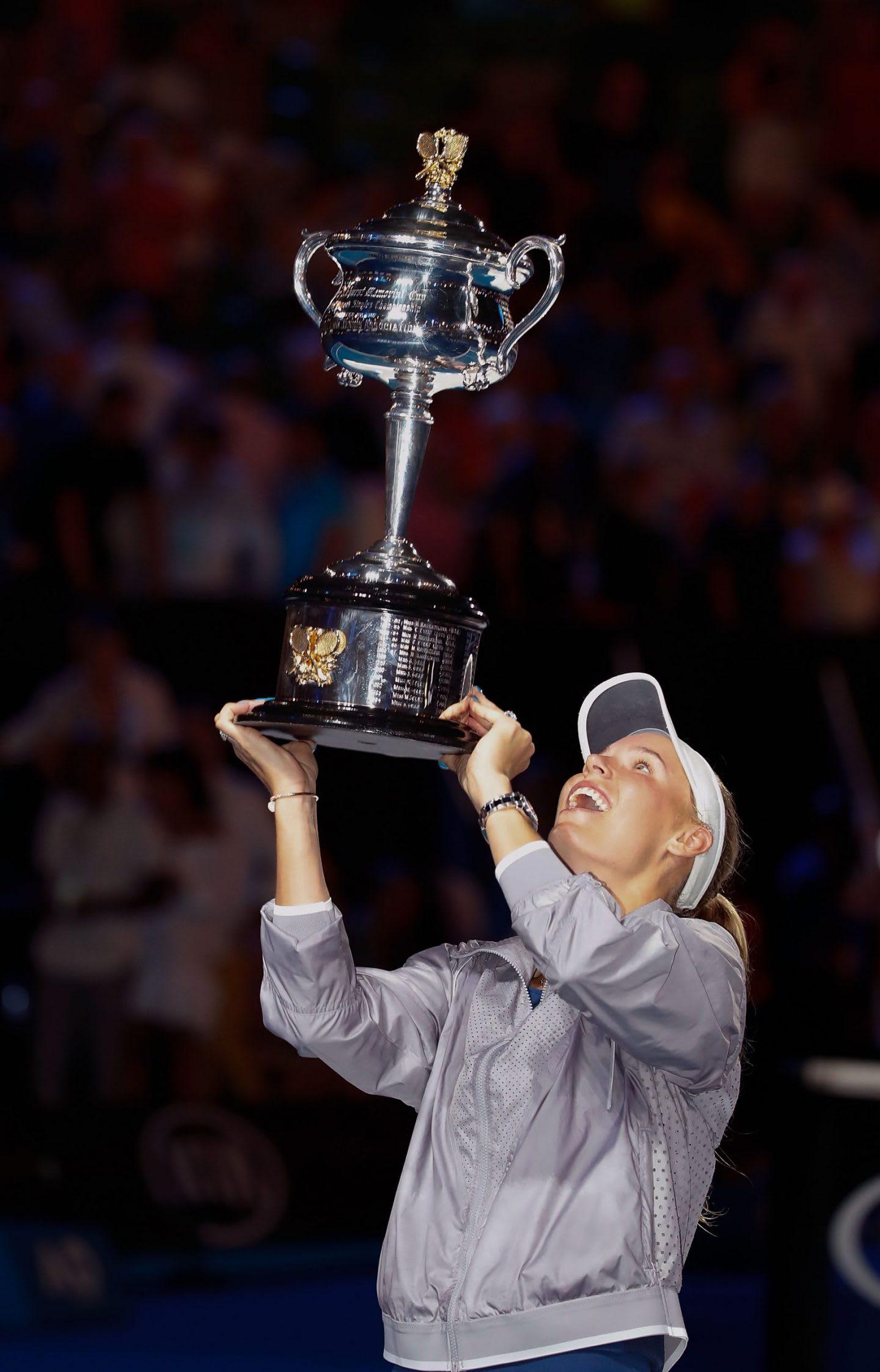 Woman wearing grey tennis outfit holding silver trophy during celebration, Caroline Wozniacki, tennis, player, Danish, athlete, Australia, Melbourne, winner