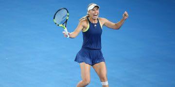 Woman wearing blue tennis outfit holding tennis racket and celebrating on blue court, Caroline Wozniacki, tennis, player, Danish, athlete, Autralia, Melbourne