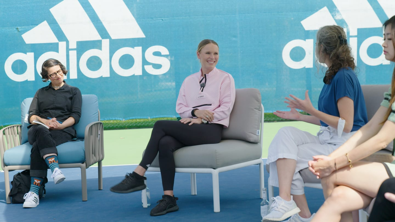 Woman wearing a pink jacket smiling while sitting on a grey chair talking to people around her, Caroline Wozniacki, tennis, player, Danish, athlete, adidas, campus, Herzogenaurach