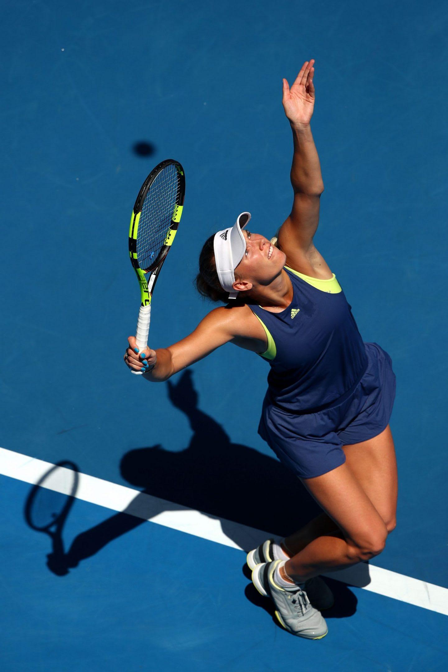 Woman in a navy tennis dress serving a ball on a blue tennis court, Caroline Wozniacki, tennis, player, Danish, athlete, sports, adidas, exercise