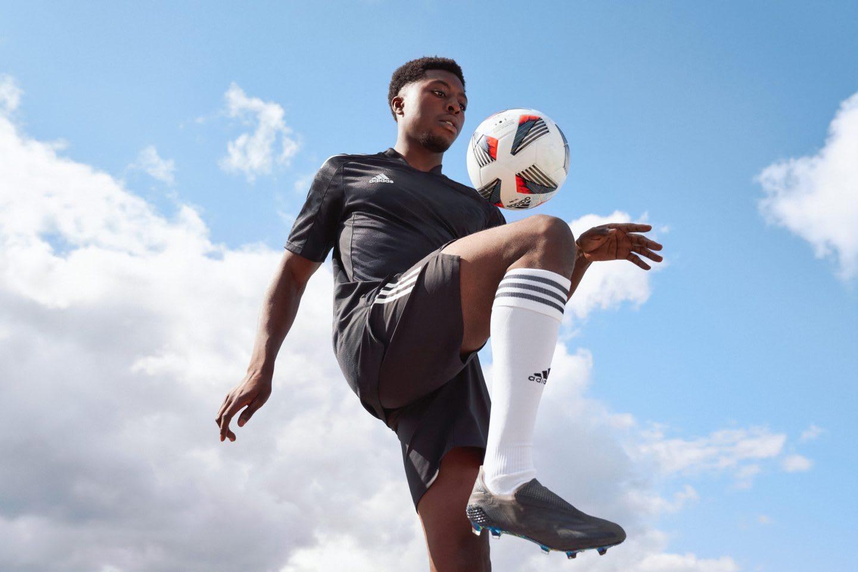 Man wearing black football uniform bouncing football ball on knee, adidas, football, athlete, performance