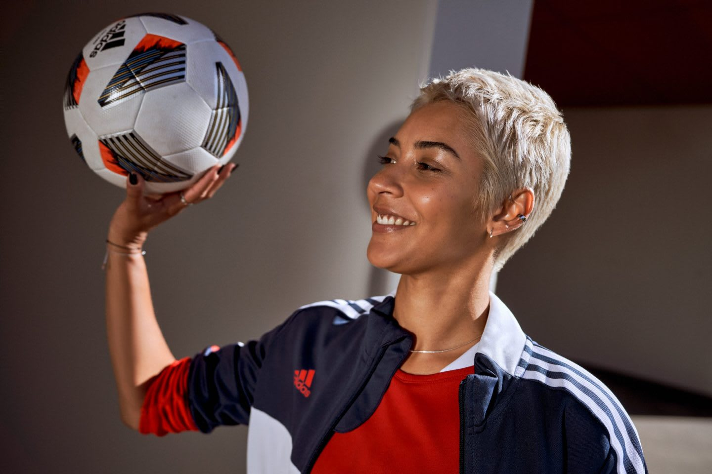 Woman with blonde short hair wearing sports outfit holding football ball in hand while smiling, adidas, football, women, inclusion