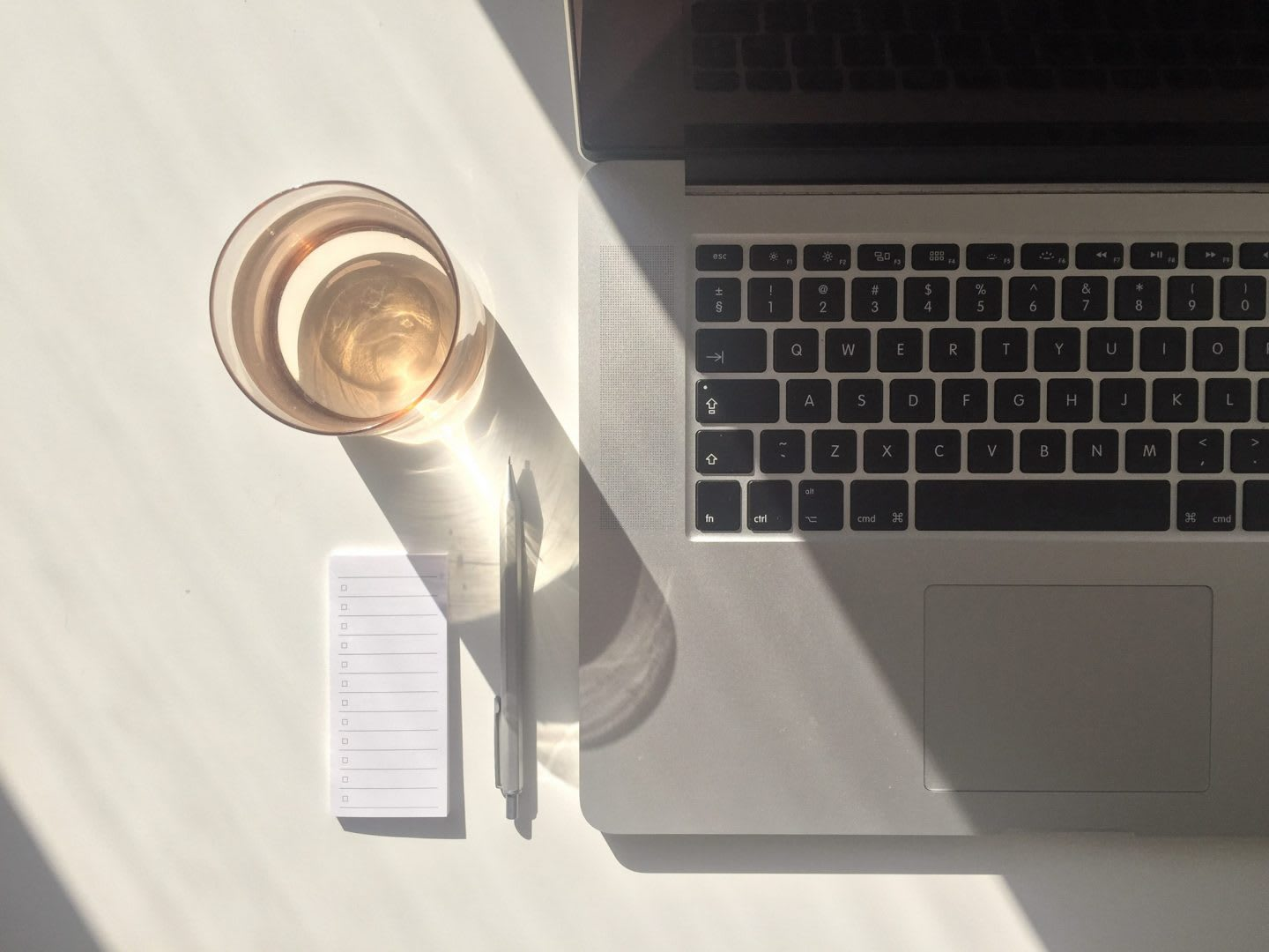 Desk with sunlight with laptop, glass of water and stationary, hydration, work, laptop, notepad