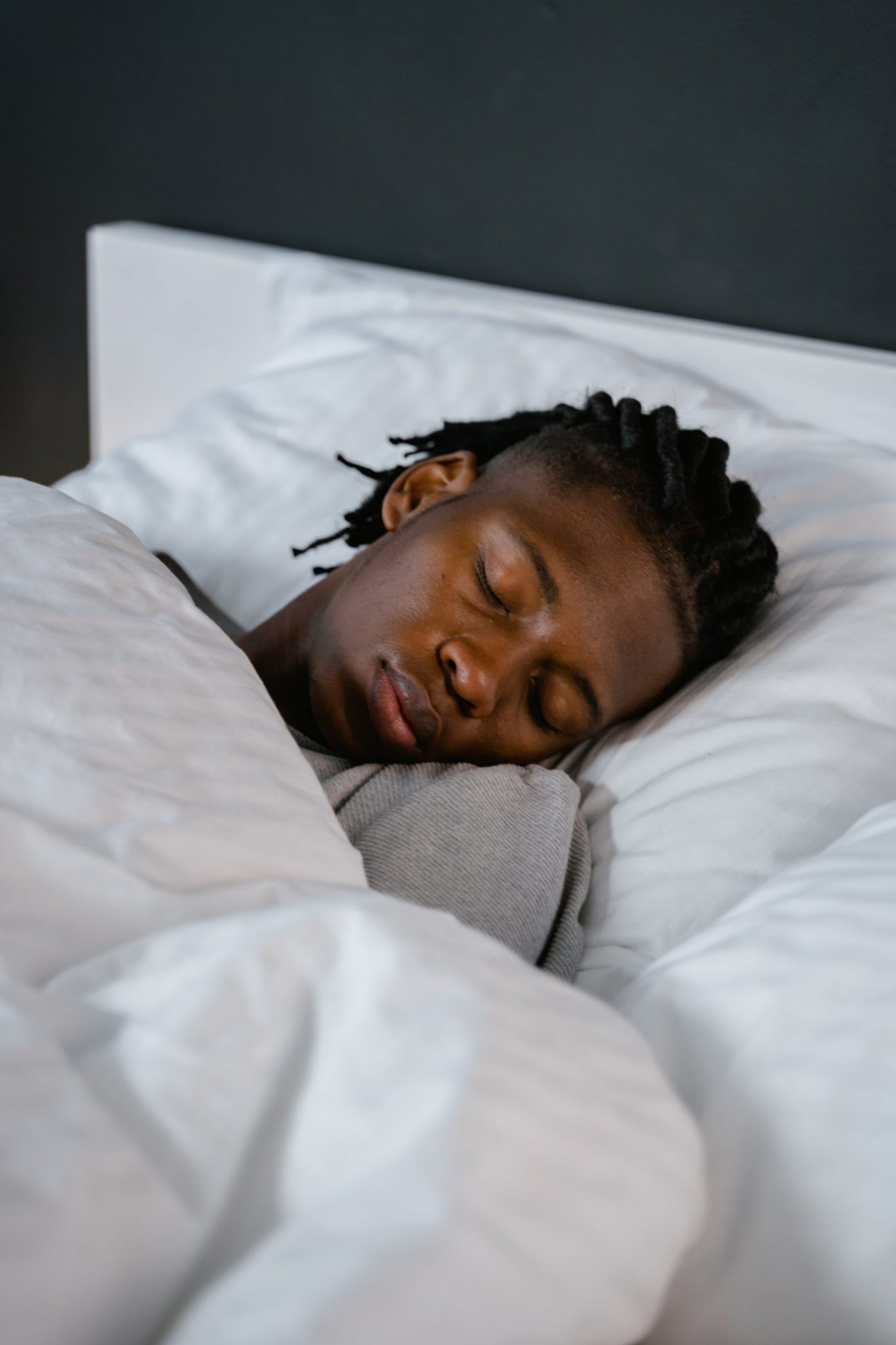 Man sleeping in a bed with white bedsheets, sleep, recovery, rest, comfortable, bed