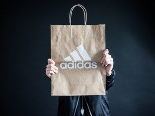 Person holding an adidas brown paper bag, sustainable, store, retail