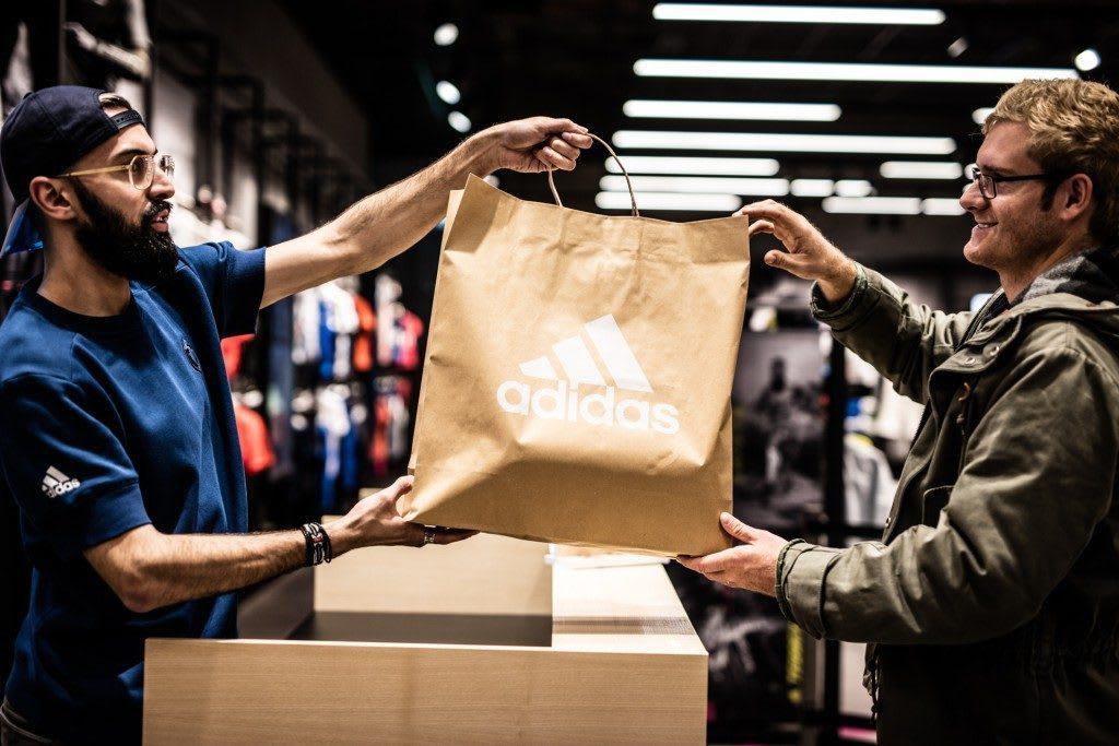 Store assistant handing over sustainable adidas brown paper bag to consumer at cashier, adidas, store, retail. sustainable, sustainability