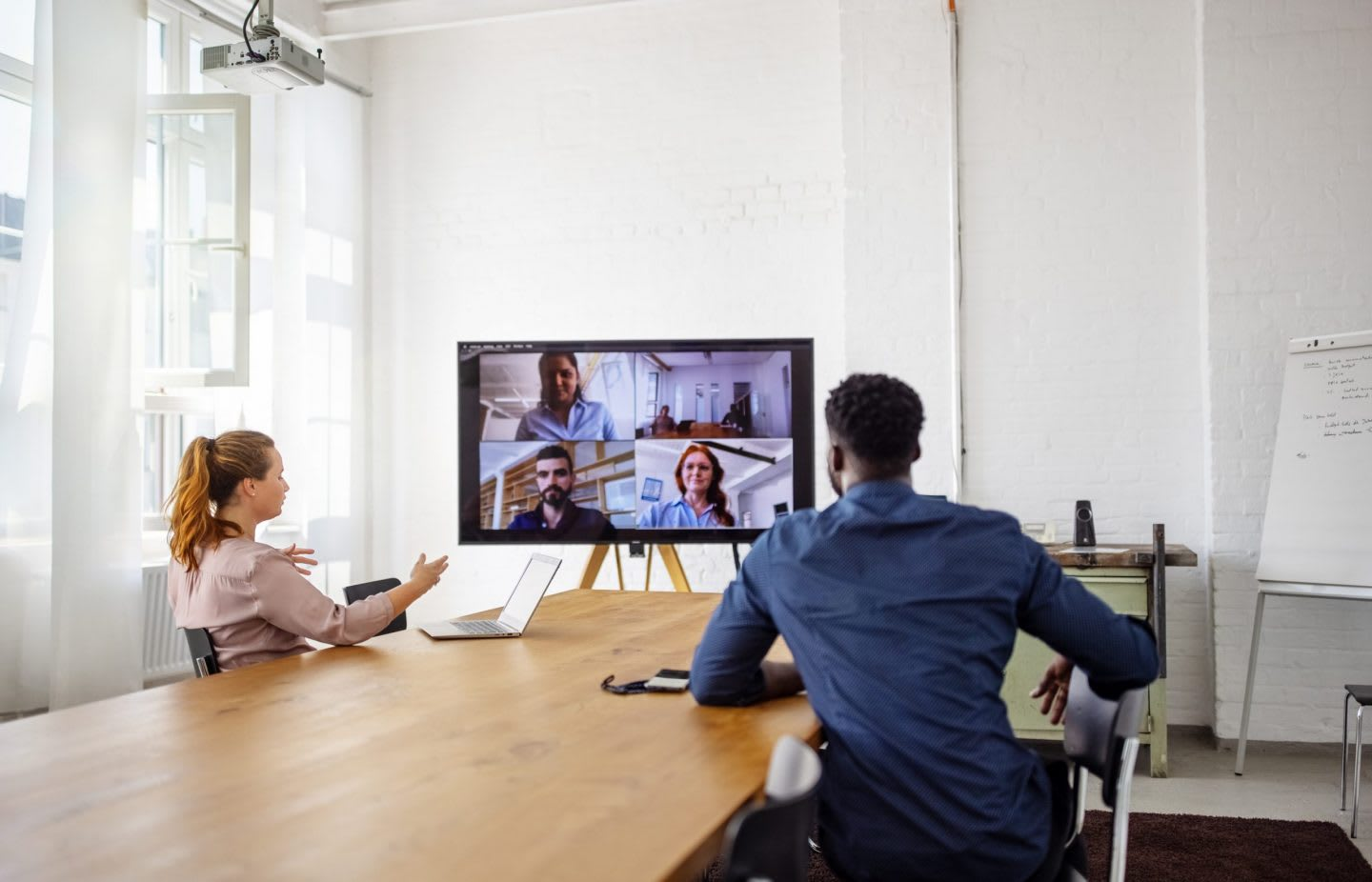 People sitting in a meeting room on a virtual call with participants, meeting, collaboration, work, discussion