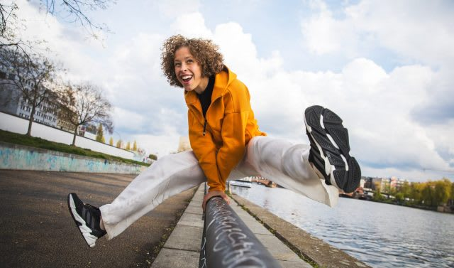 Girl wearing orange jacket and white trousers jumping over railing, adidas, sports, lifestyle, activewear, active