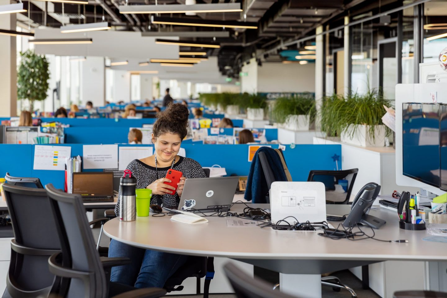 Woman looking at mobile phone in front of laptop in an open office, adidas, employee, workplace, happy, people