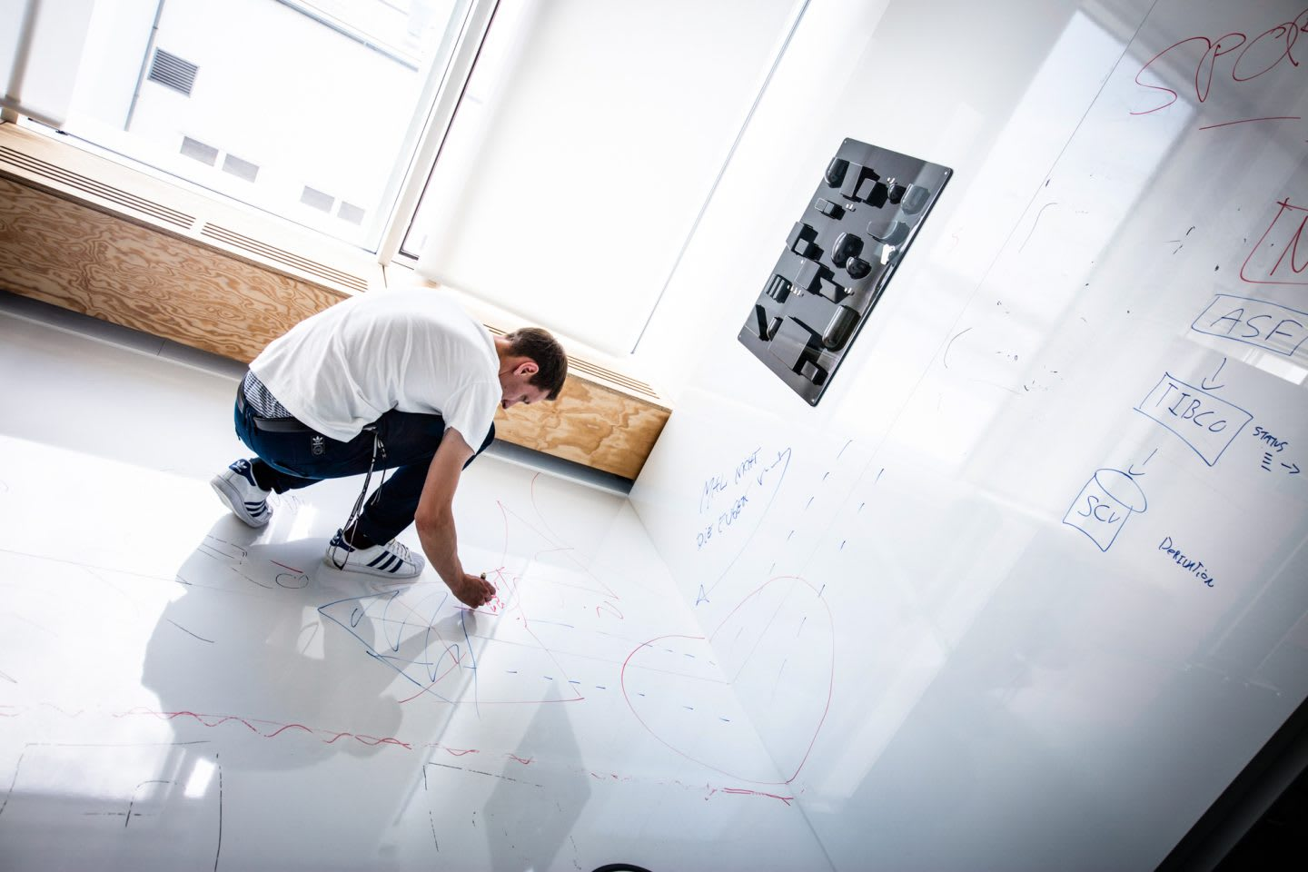 Man wearing white t-shirt writing with whiteboard markers on whiteboard walls and floor, creativity, thinking, brainstorm, ideas, adidas, workplace, employee