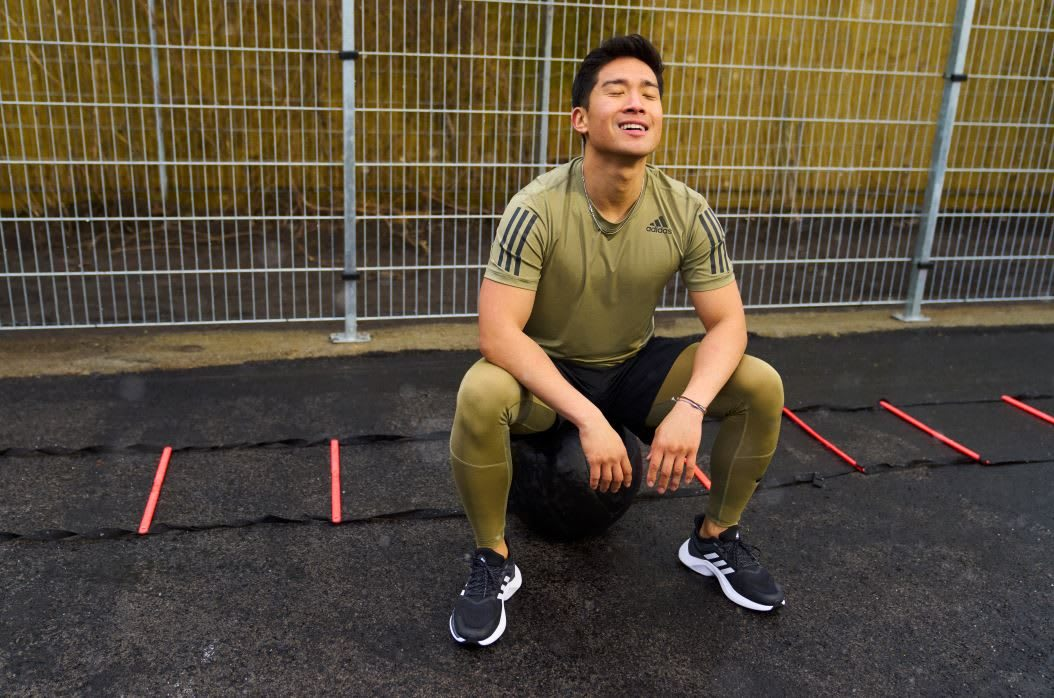 Man wearing green adidas sports t-shirt relaxing after workout in outdoor gym, adidas, sports, performance, exercise, fitness